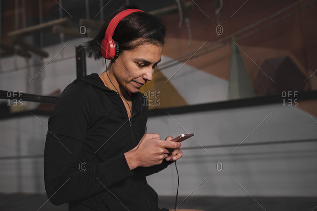 Side view of young lady in sportswear with headphones and gadget listening music and sitting in gym