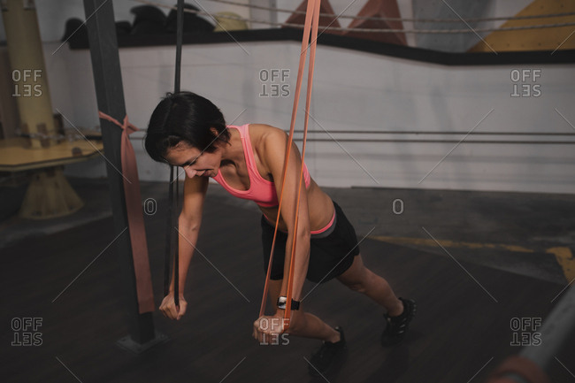 Young slim sportive lady in sportswear doing exercises with resistance band in gym