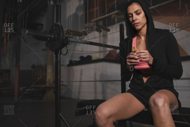 Young slim cheerful lady in sportswear with energy bar sitting on bench in gym