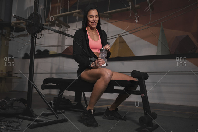 Young slim cheerful lady in sportswear with bottle of water sitting on bench in gym