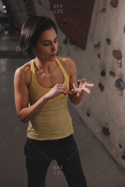 Young lady in sportswear fixing finger tape near wall with climbing holds in gym