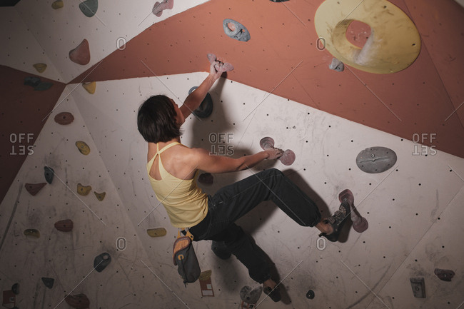 Back view of young lady in sportswear training on climbing wall with holds in gym