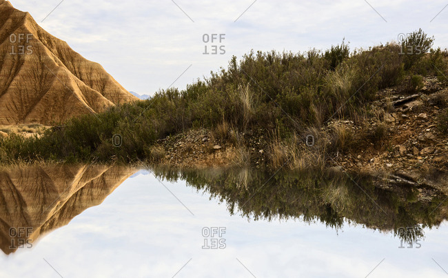 Water surface near shore with stone mountains in Bardenas Reales, Navarra, Spain