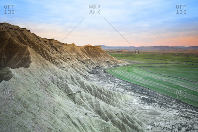 From above amazing view of stone mountains near green meadows and blue sky in Bardenas Reales, Navarra, Spain