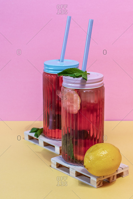 Jars of pink cold ice tea with straw and lemon and in a wooden pallets