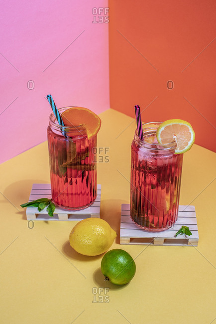 Jars of pink cold ice tea with straw and lemon and lime in a wooden pallets