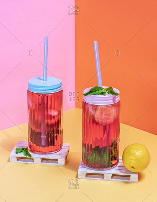 Jars of pink cold ice tea with straw and lemon in a wooden pallets