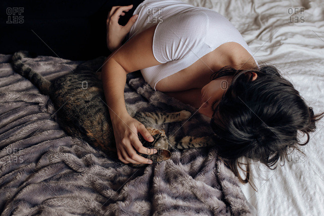 Cute young female lying on comfortable bed and stroking adorable cat at home