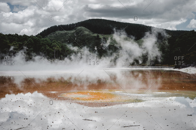 Thick vapor floating over surface of beautiful Rotorua lake on cloudy day in New Zealand