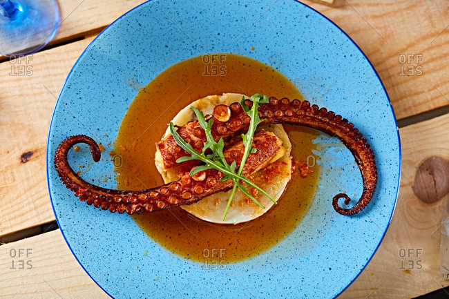 Squid arms served with sauce on polenta on blue plate
