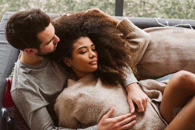 Young multiracial couple hugging on sofa