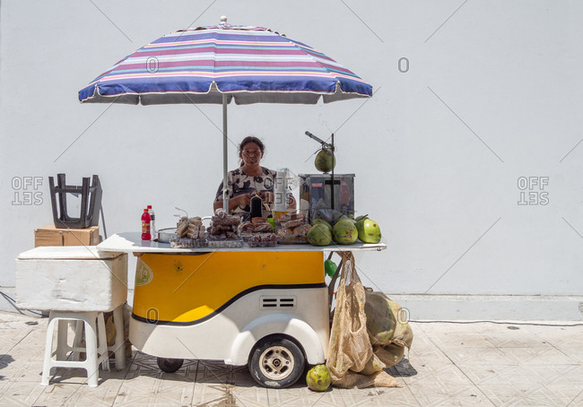 Rio de Janeiro, Brazil - February 13 2014: Adult female sitting behind modern kiosk and selling fresh coconuts on street of Florianopolis in Brazil