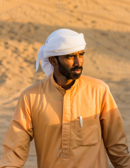 United Arab Emirates - May, 25 2013: Bearded ethnic man in traditional clothes looking away while walking in desert on sunny day