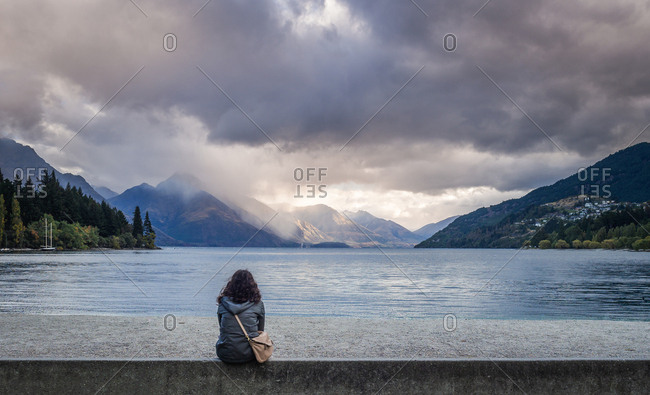 Christchurch, New Zealand - March, 17 2015: Back view of female in casual outfit looking at calm lake and amazing mountains on cloudy day