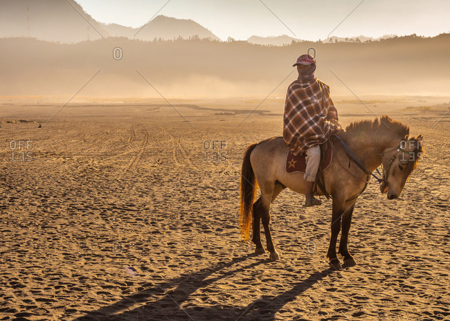 Java Island, Indonesia - August, 14 2015: Anonymous person on horse near volcano