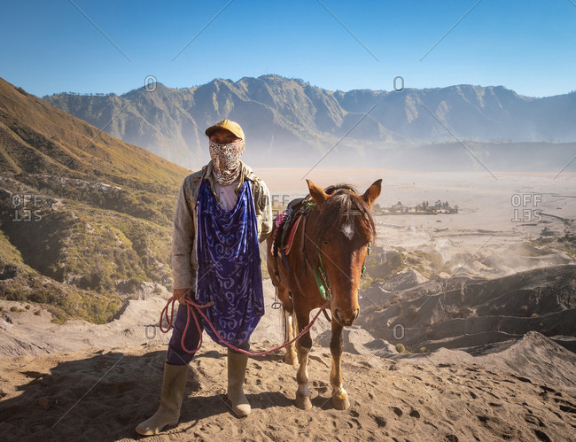 Java Island, Indonesia - August, 14 2015: Ethnic person with scarf on face looking at camera while standing near lovely horse not far from Mount Bromo on sunny day