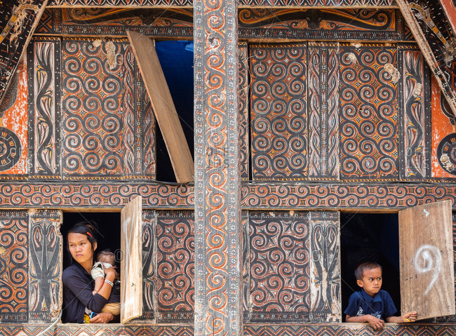 Bali, Indonesia - August, 15 2015: Ethnic woman with infant and funny boy looking out windows of shabby ornamental house in village