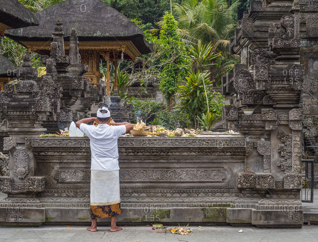 Bali, Indonesia - August, 15 2015: Anonymous man standing near table with religious gifts