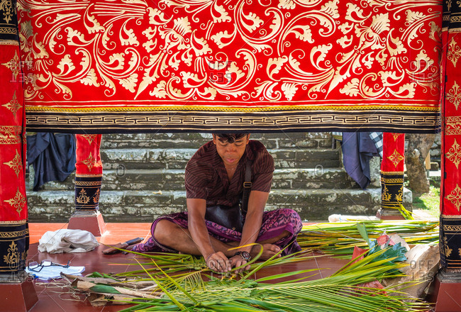 Bali, Indonesia - August, 15 2015: Adult ethnic male in traditional clothes braiding fresh palm leaves while sitting in ornamental tent near temple