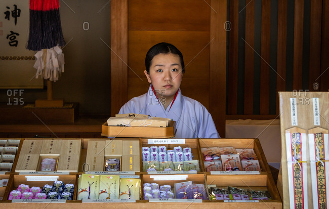 Japan - May, 10 2013: Pretty Asian female in traditional clothes standing behind stall with various souvenirs on city street