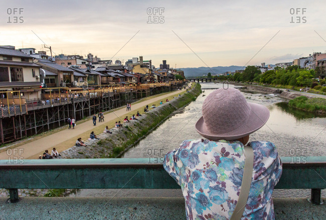 Japan - May, 10 2013: Back view of person leaning on bridge railing and looking at small river and lovely city