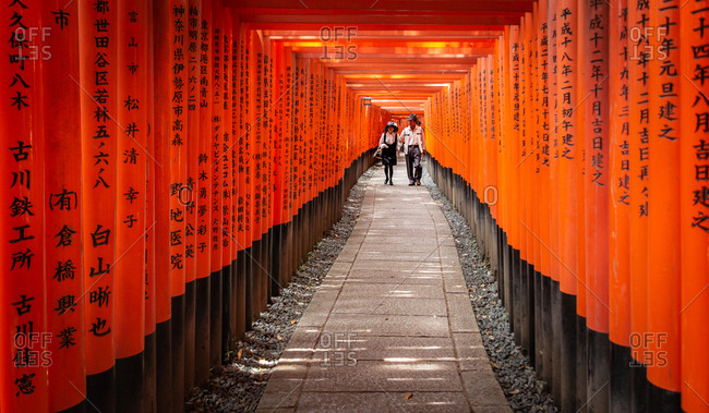 Japan - May, 10 2013: Two people walking amidst red pillars with writings in narrow archway in Shinto shrine