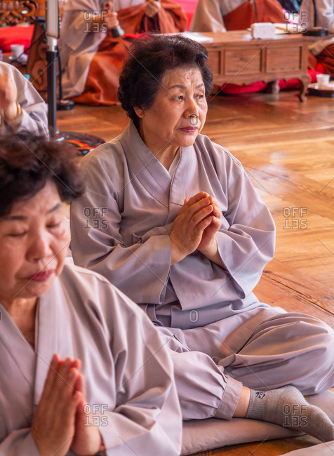 Seoul, South Korea - August, 08 2017: Senior Asian females in traditional clothing clasping hands and praying while sitting on floor in temple