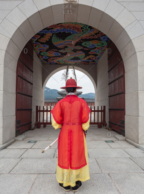 Seoul, South Korea - August, 08 2017: Back view of male in bright traditional clothes standing near beautiful archway
