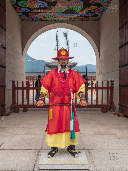 Busan, South Korea - August, 05 2017: Asian man in traditional warrior clothes standing near archway on sunny day