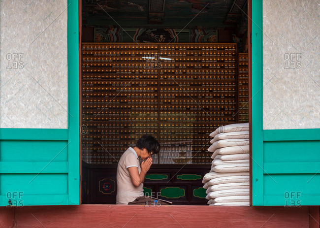 Busan, South Korea - August, 05 2017: Side view of Asian female sitting near stack of pillows and praying inside traditional house