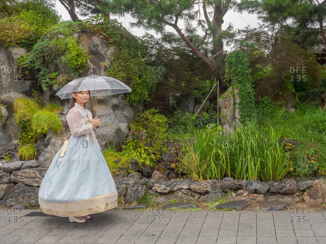 Seoul, South Korea - August, 08 2017: Side view of lovely young Asian female in traditional garment holding transparent umbrella and looking at camera while standing in amazing park
