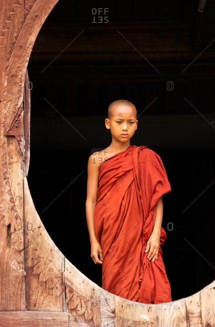 Mandalay, Myanmar - June, 25 2012: Bald ethnic boy in monk apparel standing inside shabby monastery building