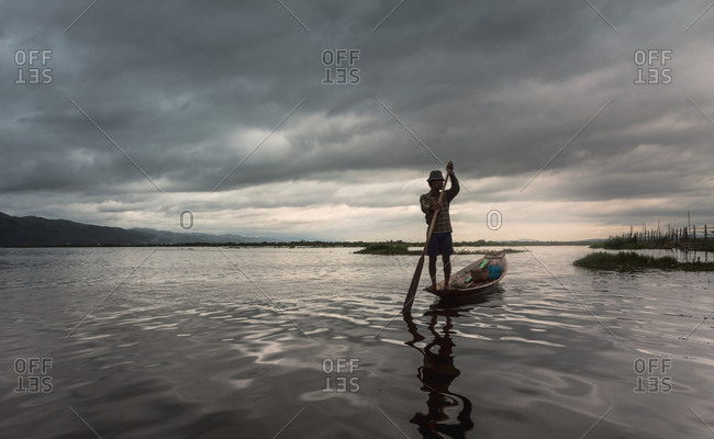 Shan, Myanmar - June, 25 2012: Anonymous fisherman standing on boat