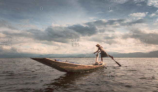 Shan, Myanmar - June, 25 2012: Side view of unrecognizable ethnic man standing and balancing on wooden boat in middle of Inle Lake on cloudy day
