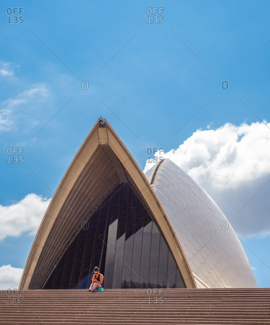 Sydney, Australia - March, 04 2015: Young woman sitting on steps near famous opera house against blue cloudy sky on sunny day