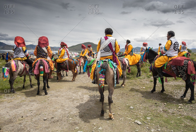 Tibet - August, 29 2014: Back view of local men in bright clothes sitting on horses against gray overcast sky