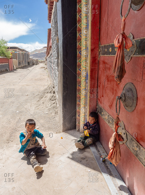 Tibet - August, 29 2014: Two little ethnic boys sitting near gate of Buddhist monastery on sunny day in town