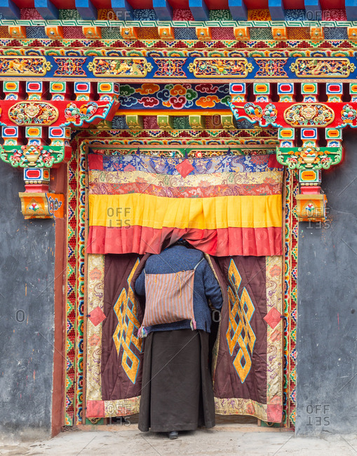 Tibet - August, 29 2014: Back view of local female standing in brightly decorated entrance of Buddhist temple