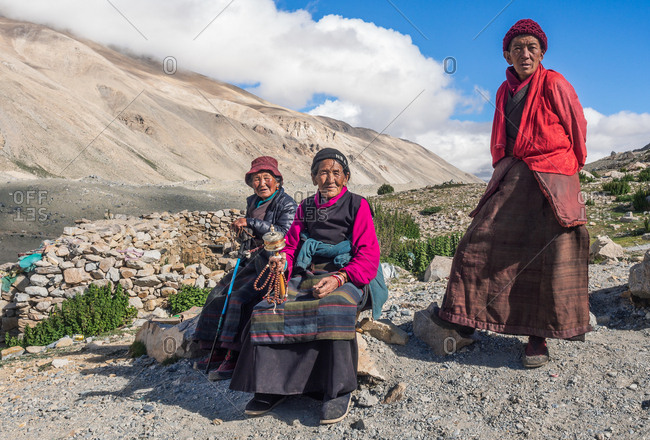 Tibet - August, 29 2014: Three senior ethnic females in traditional clothes looking at camera on sunny day in mountains