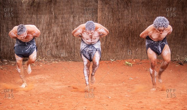 Uluru Outback, Australia - March, 09 2015: Three male aborigines with paint on skin dancing traditional dance on sand together