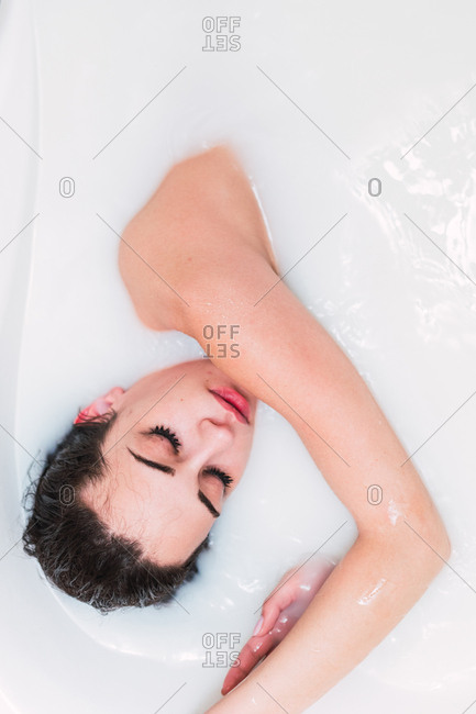 Seductive young female keeping eyes closed while lying in bathtub full of warm milk