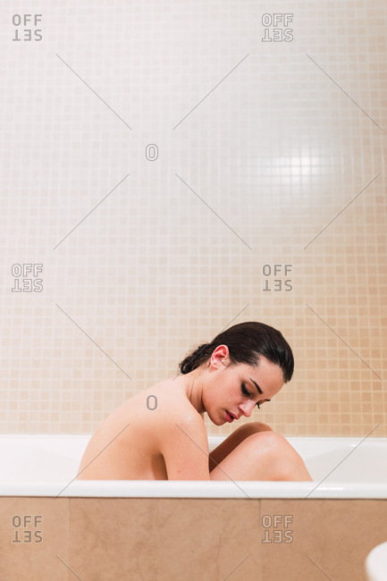 Side view of naked female keeping eyes closed while sitting in bathtub in stylish bathroom