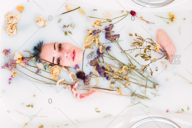 Lovely young lady lying in bathtub with white water and dried flowers and looking at camera