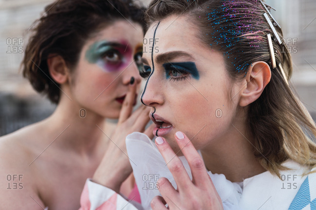 Two young women with theatrical makeup and unusual clothes sharing secret while performing on city street