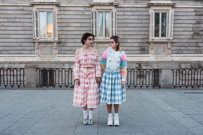 Two young women with theatrical makeup and unusual clothes performing on city street