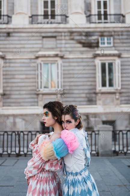 Side view of Two young women with theatrical makeup and unusual clothes performing and hugging on city street