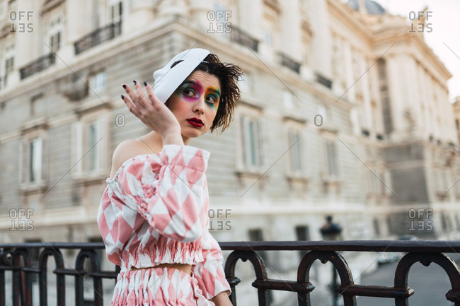 Young woman with theatrical costume and white mask while acting on street of city