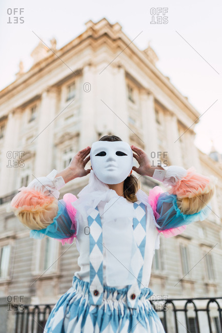 Anonymous young woman wearing theatrical costume and white mask while acting on street of city