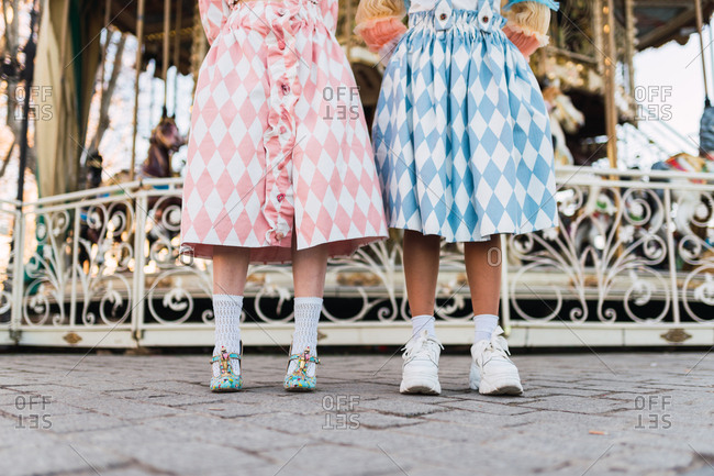 crop legs of young women with theatrical clothes standing near merry-go-round on fairground
