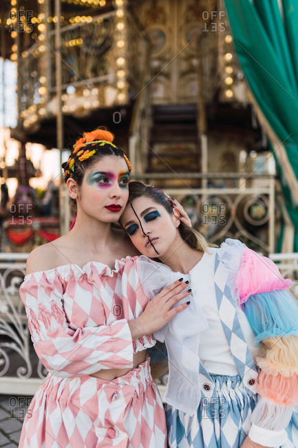 Beautiful young woman with theatrical makeup embracing friend and looking away while standing near merry-go-round on fairground
